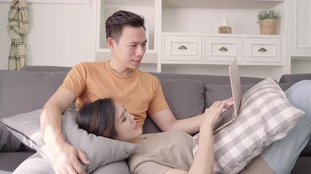Asian couple using laptop for search web in living room at home, sweet couple enjoy love moment while lying on the sofa when relax at home. Lifestyle couple relax at home concept.