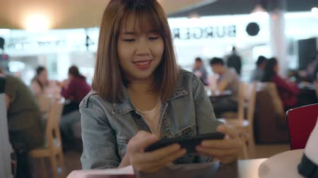 raam : Happy Asian woman using and checking her smartphone while sitting on chair in terminal hall while waiting her flight at the departure gate in international airport. Women happy in airport concept. Stockvideo