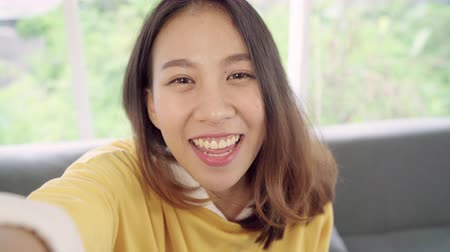 Asian blogger woman using smartphone recording vlog video in living room at home,female enjoy funny moment while lying on the sofa when relax at home. Lifestyle blogger making video at home.