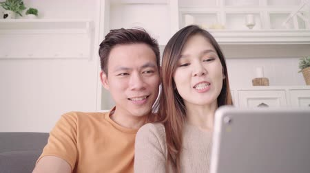 Asian couple using tablet VIDEO Call with friend in living room at home, sweet couple enjoy love moment while lying on the sofa when relaxed at home. Lifestyle couple relax at home concept.