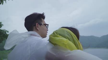 Slow motion - Young Asian sweet couple feeling happy using romantic time playing rain while wearing raincoat standing near lake. Lifestyle couple enjoy and relax in rainy day.