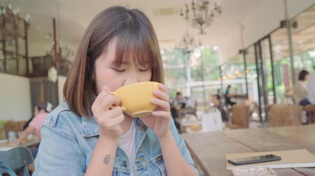 Business freelance Asian woman drinking warm cup of green tea or coffee while sitting on table in cafe. Lifestyle smart beautiful female relax in coffee shop concepts.