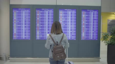 Happy Asian woman looking at information board checking her flight with luggage in terminal hall at the departure gate in international airport. Lifestyle women happy in airport concept. 影像素材