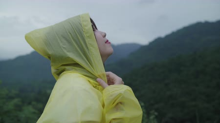 Young Asian woman feeling happy playing rain while wearing raincoat walking near forest. Lifestyle women enjoy and relax in rainy day.