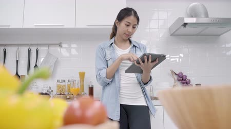 vitamina : Happy Asian woman using tablet for looking recipe while making food in the kitchen, female use organic vegetable for healthy food at home. Lifestyle women making food concept.