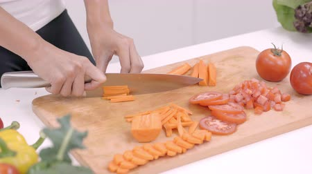 placa de corte : Happy Asian woman cut lots of carrot prepare ingredient for making food in the kitchen, female use organic vegetable for healthy food at home. Lifestyle women making food concept. Stock Footage