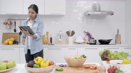 Happy Asian woman using tablet for looking recipe while making food in the kitchen, female use organic vegetable for healthy food at home. Lifestyle women making food concept.