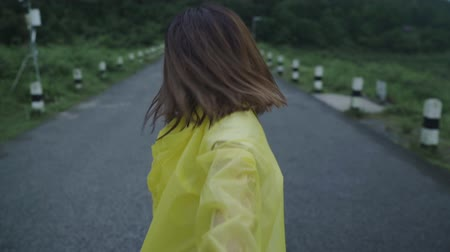 Slow motion - Young Asian woman feeling happy playing rain while wearing raincoat walking near forest. Lifestyle women enjoy and relax in rainy day.