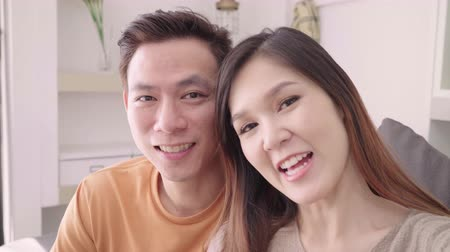 descontraído : Asian couple using smartphone VIDEO Call with friend in living room at home, sweet couple enjoy love moment while lying on the sofa when relaxed at home. Lifestyle couple relax at home concept. Vídeos