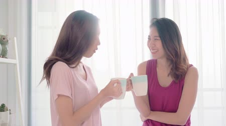 Young Asian women lesbian happy couple talking and drinking coffee in bedroom at home, enjoy love moment while lying on bed when relaxed in morning. Lifestyle LGBT couple together indoors concept. 影像素材
