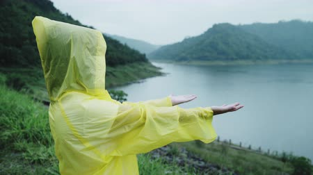 Young Asian woman feeling happy playing rain while wearing raincoat standing near lake. Lifestyle women enjoy and relax in rainy day.