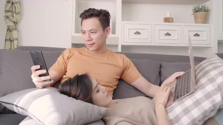 Asian couple using smartphone and laptop checking social media in living room at home, sweet couple enjoy love moment while lying on sofa when relaxed at home. Lifestyle couple relax at home concept. 影像素材