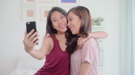 Young Asian women lesbian happy couple using smartphone for selfie in bedroom at home, sweet couple enjoy love moment while lying on bed when relaxed. Lifestyle LGBT couple together indoors concept.