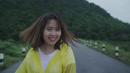 fırtına : Slow motion - Young Asian woman feeling happy playing rain while wearing raincoat walking near forest. Lifestyle women enjoy and relax in rainy day.