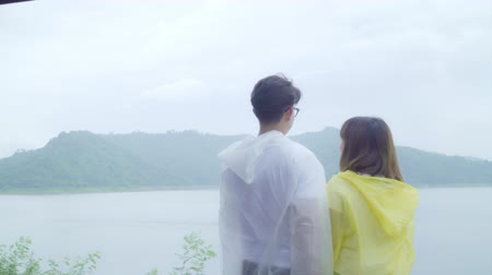 fırtına : Slow motion - Young Asian sweet couple feeling happy using romantic time playing rain while wearing raincoat standing near lake. Lifestyle couple enjoy and relax in rainy day.
