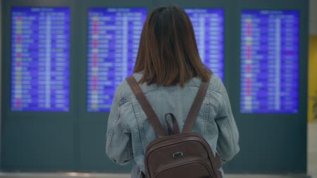 pasaport : Slow motion - Happy Asian woman looking at information board checking her flight with luggage in terminal hall at the departure gate in international airport. Lifestyle women happy in airport concept.