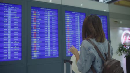 Slow motion - Happy Asian woman looking at information board checking her flight with luggage in terminal hall at the departure gate in international airport. Lifestyle women happy in airport concept.