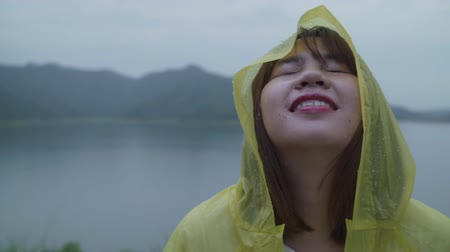 fırtına : Slow motion - Young Asian woman feeling happy playing rain while wearing raincoat standing near lake. Lifestyle women enjoy and relax in rainy day. Stok Video