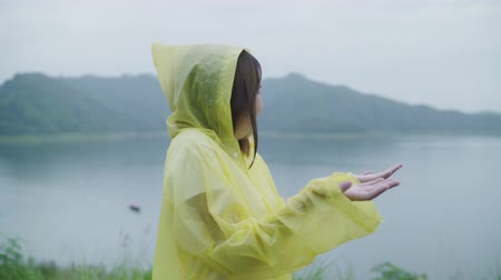 Slow motion - Young Asian woman feeling happy playing rain while wearing raincoat standing near lake. Lifestyle women enjoy and relax in rainy day. Wideo