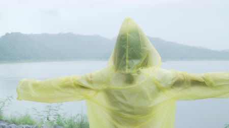 fırtına : Young Asian woman feeling happy playing rain while wearing raincoat standing near lake. Lifestyle women enjoy and relax in rainy day.