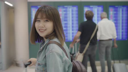 pasaport : Happy Asian woman looking at information board checking her flight with luggage in terminal hall at the departure gate in international airport. Lifestyle women happy in airport concept. Stok Video