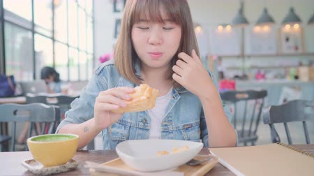 çay : Business freelance Asian woman eating bread and drinking warm cup of coffee while sitting on table in cafe. Lifestyle smart beautiful female relax in coffee shop concepts.