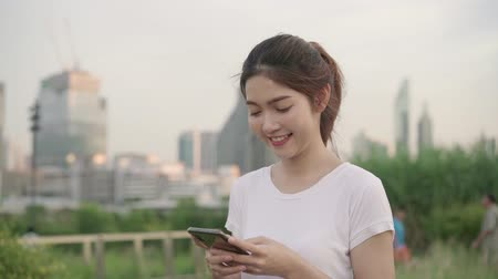 rugzak : Slow motion - Cheerful Asian tourist blogger woman using smartphone for direction and looking on location map while traveling on the street at city. Lifestyle backpack tourist travel holiday concept. Stockvideo