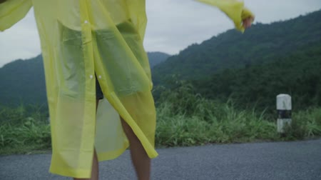 dişlek : Slow motion - Young Asian woman feeling happy playing rain while wearing raincoat walking near forest. Lifestyle women enjoy and relax in rainy day.