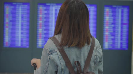 inchecken : Slow motion - Happy Asian woman looking at information board checking her flight with luggage in terminal hall at the departure gate in international airport. Lifestyle women happy in airport concept.