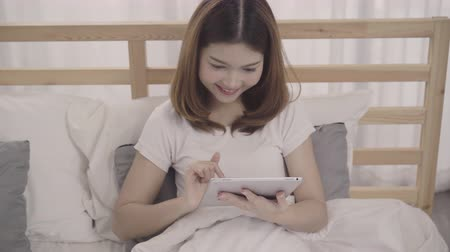 tek başına : Young Asian woman using tablet while lying on bed after wake up in the morning, Beautiful attractive Japanese girl smiling relax in bedroom at home. Enjoying time lifestyle women at home concept.