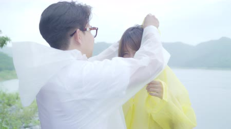 fırtına : Young Asian sweet couple feeling happy using romantic time playing rain while wearing raincoat standing near lake. Lifestyle couple enjoy and relax in rainy day.