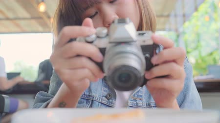 revisão : Food blogger Asian woman using camera for photo dessert, bread and drink while sitting on table in cafe. Lifestyle beautiful women relax at coffee shop concepts.