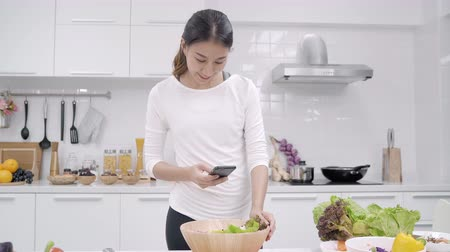 vitamina : Young Asian blogger woman using smartphone photo post in social media in the kitchen, female making salad at home. Lifestyle women relax at home concept. Stock Footage