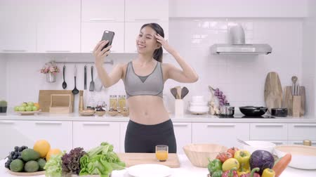 写真 : Young Asian blogger woman using smartphone selfie herself in the kitchen, female in sport clothing cooking at home. Lifestyle women relax at home concept.