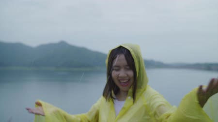 chuveiro : Slow motion - Young Asian woman feeling happy playing rain while wearing raincoat standing near lake. Lifestyle women enjoy and relax in rainy day. Vídeos