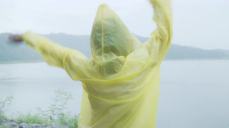 chuveiro : Young Asian woman feeling happy playing rain while wearing raincoat standing near lake. Lifestyle women enjoy and relax in rainy day.