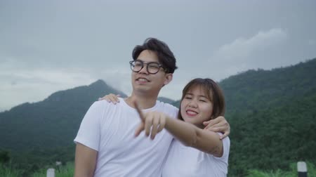 perspektif : Hiker backpacker couple on hiking adventure feeling freedom walking in forest near lake in rainy day. Lifestyle couple travel relax using romantic time concept. Stok Video