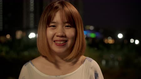 иероглиф : Cheerful beautiful young Asian woman feeling happy smiling to camera while traveling on street at downtown city in the night. Lifestyle tourist travel holiday concept. Portrait looking at camera.