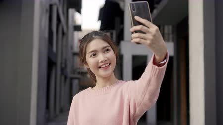 viver : Cheerful beautiful young Asian backpacker blogger woman using smartphone taking selfie while traveling at Chinatown in Beijing, China. Lifestyle backpack tourist travel holiday concept.