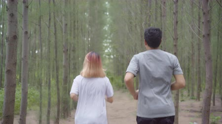 спринт : Healthy young athletic sporty Asian runner man and woman in sports clothing running and jogging on forest trail. Lifestyle fit and active women exercise in the forest concept. Стоковые видеозаписи