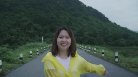 chuveiro : Slow motion - Young Asian woman feeling happy playing rain while wearing raincoat walking near forest. Lifestyle women enjoy and relax in rainy day.