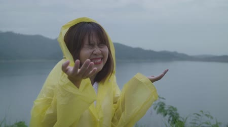 regenjas : Slow motion - Young Asian woman feeling happy playing rain while wearing raincoat standing near lake. Lifestyle women enjoy and relax in rainy day. Stockvideo