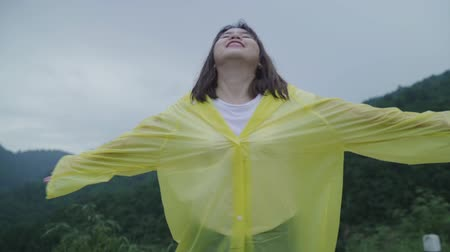 andar : Slow motion - Young Asian woman feeling happy playing rain while wearing raincoat walking near forest. Lifestyle women enjoy and relax in rainy day.