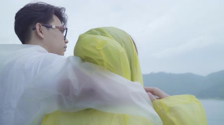 objetí : Slow motion - Young Asian sweet couple feeling happy using romantic time playing rain while wearing raincoat standing near lake. Lifestyle couple enjoy and relax in rainy day.