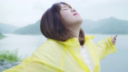 impermeabile : Young Asian woman feeling happy playing rain while wearing raincoat standing near lake. Lifestyle women enjoy and relax in rainy day.