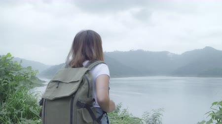 backpacken : Hiker backpacker woman on hiking adventure feeling freedom walking in forest near lake in rainy day. Lifestyle women travel relax concept.