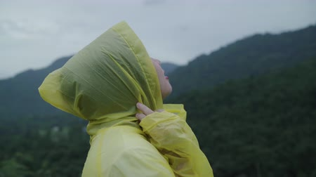 chuveiro : Young Asian woman feeling happy playing rain while wearing raincoat walking near forest. Lifestyle women enjoy and relax in rainy day.