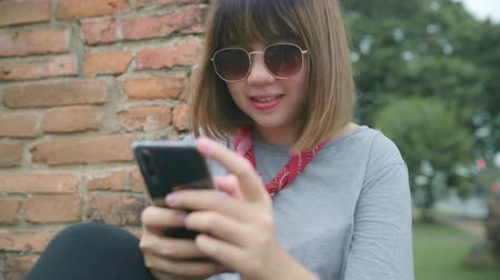 navegar : Traveler Asian woman using smartphone checking social media while relax after spending holiday trip at Ayutthaya, Thailand, female enjoy her journey at amazing landmark in traditional city.