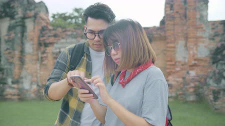 navigatie : Traveler Asian couple using smartphone for direction and looking on location map while spending holiday trip at Ayutthaya, Thailand, backpacker sweet couple enjoy journey in traditional city.