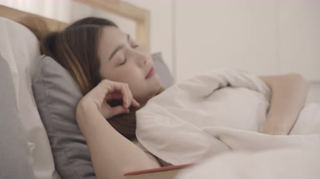 journaal : Beautiful young Asian woman reading a book while lying on the bed, Female sleep after relax in bedroom at home. Lifestyle women using relax time at home concept. Stockvideo